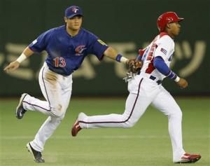 Yung Chi Chen tags out a Cuban base runner for Taiwan. (Photo Credit: Koji Sasahara / AP)