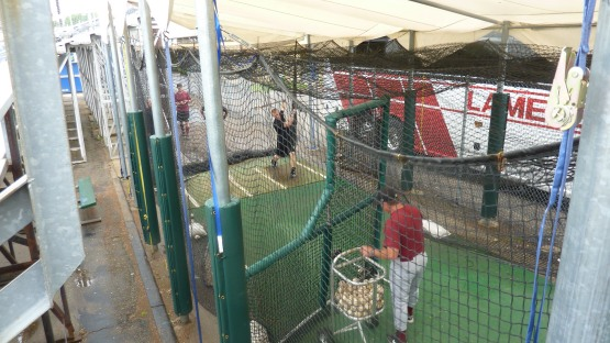 Michael Reed works with Dusty Rhodes in the cage at Pohlman Field before Tuesday's game.
